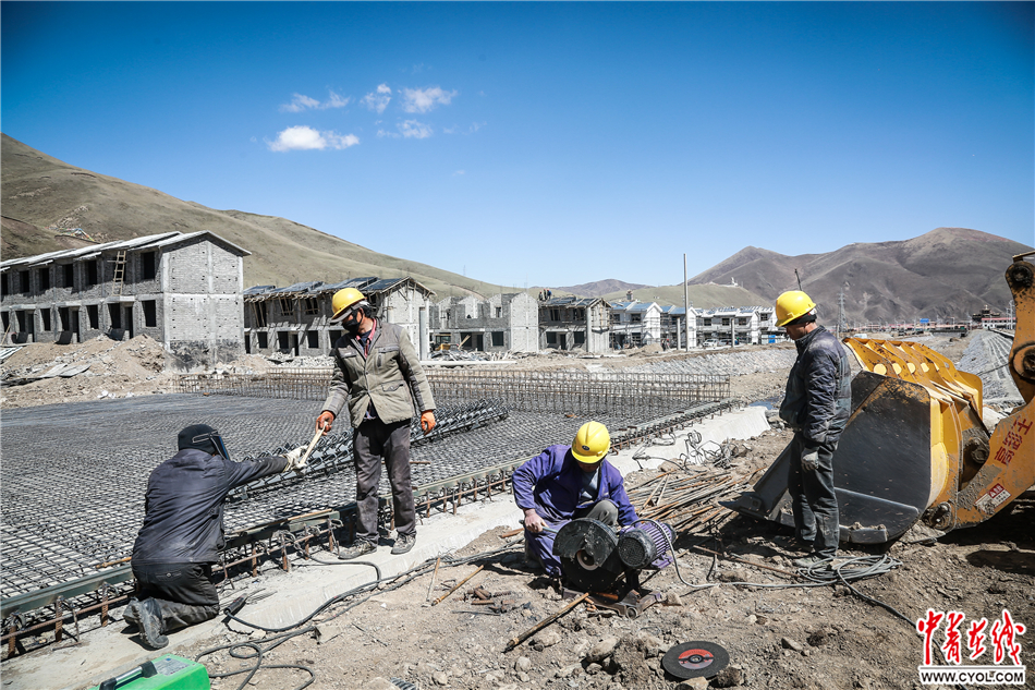 2017年5月18日,青海省果洛藏族自治州达日县城,几名工人在易地扶贫搬迁房项目工地上工作。据介绍,县城中集中安置的易地搬迁房每户建筑面积79.4平方米,格局为两层藏式小楼房,并配套建设水电路、土暖设施。中国青年报·中青在线记者 赵迪/摄
