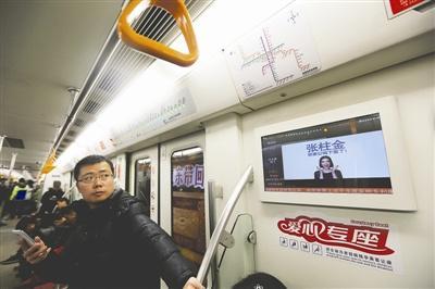 """17日2号线上,""""张柱金,你家公鸡下蛋了!""""的广告影响了乘客。 摄影/陶轲 张建"""