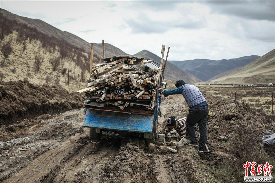 2017年5月22日,青海省果洛藏族自治州达日县上红科乡哈青村,两名参与易地扶贫搬迁项目的工人在救援陷入泥坑的车。他们车上装满了易地搬迁项目工地上的建筑材料。中国青年报·中青在线记者 赵迪/摄